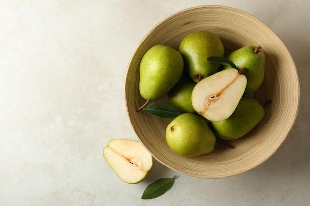 Ciotola con pere verdi su bianco strutturato Foto Premium