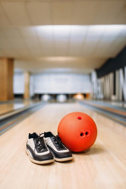 Palla da bowling e scarpe da casa sulla corsia del club, birilli, nessuno. concetto di gioco della ciotola, tenpin Foto Premium