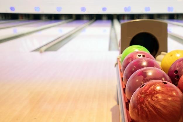 Sfere di bowling su una pila con il fondo del vicolo di bowling Foto Premium