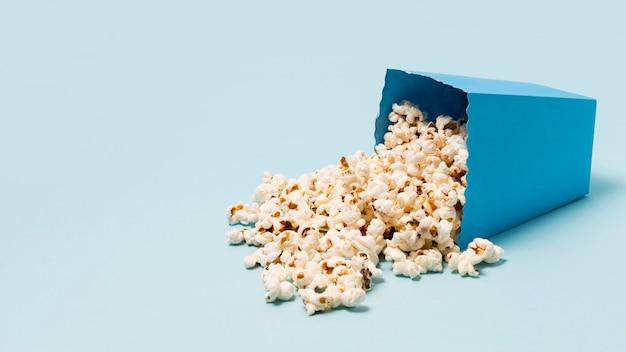 Scatola di popcorn versato su sfondo blu Foto Premium