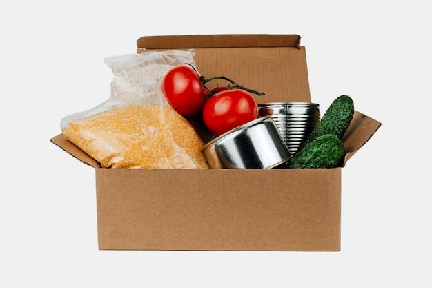 Scatola con prodotti. verdure, cereali e prodotti in scatola in una scatola di cartone isolata. Foto Premium