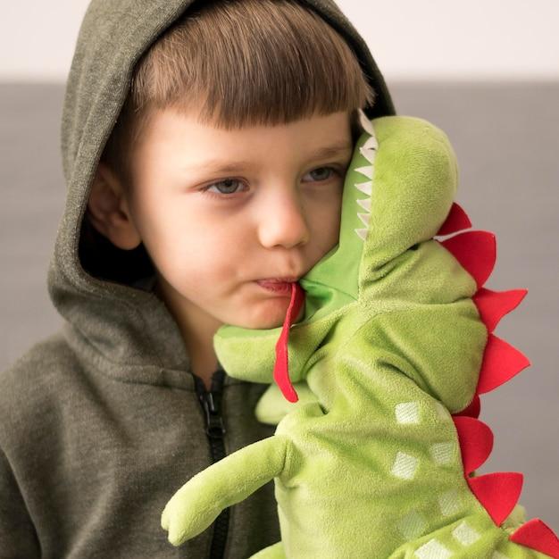 Ragazzo in costume di dinosauro con giocattolo Foto Premium