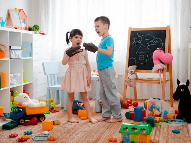 Ragazzo e ragazza bambini che gridano con i dinosauri giocattolo e che giocano nella stanza dei bambini. Foto Premium
