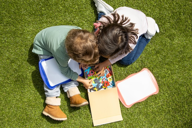 Un ragazzo e una ragazza giocano con le lettere dell'alfabeto in giardino. scuola a casa. Foto Premium