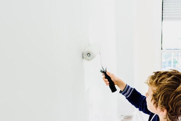Il ragazzo aiuta la sua famiglia a dipingere un muro bianco. Foto Premium