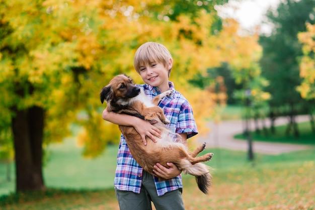 Ragazzo che abbraccia un cane e plyaing con nel parco cittadino di autunno Foto Premium