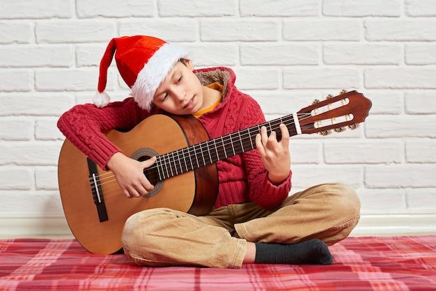 Ragazzo che suona la chitarra acustica di musica vestito con un maglione rosso e un cappello della santa Foto Premium