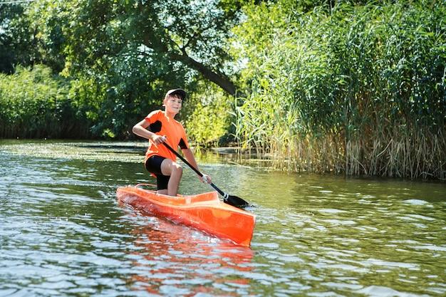 Il ragazzo che rema in canoa sul fiume Foto Premium