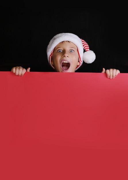 Ragazzo in cappello di babbo natale che grida e che tiene la carta bianca rossa per gli auguri di natale. isolato sul nero Foto Premium
