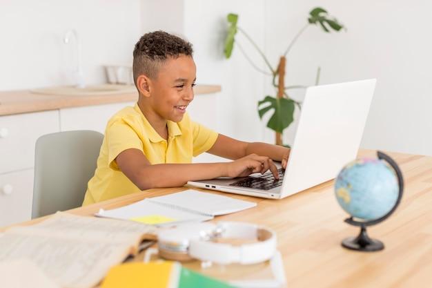 Ragazzo che sorride esaminando computer portatile Foto Premium