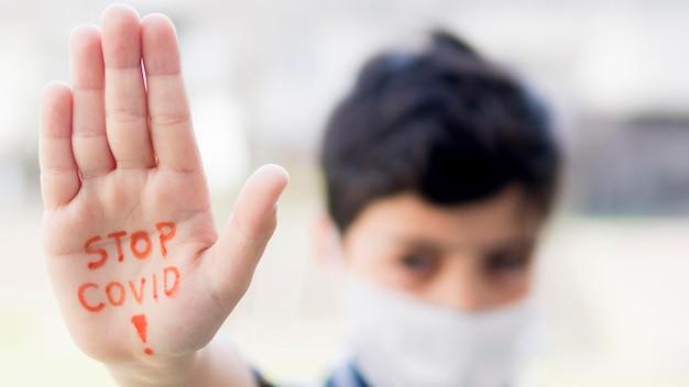 Ragazzo con stop coronavirus messaggio a portata di mano Foto Premium