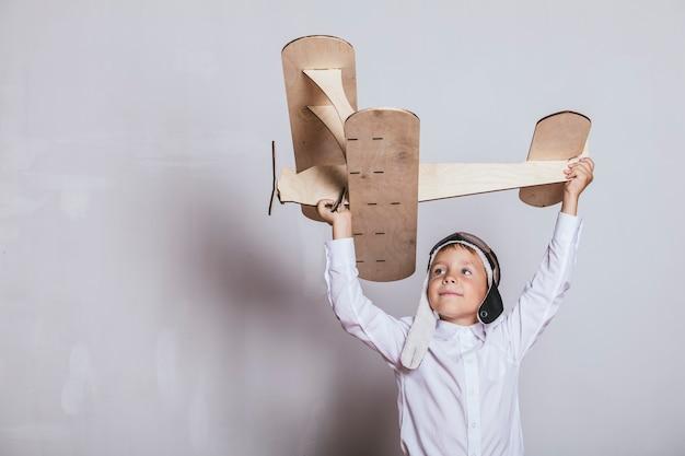 Ragazzo con modello di aereo in legno e berretto con cappuccio Foto Premium