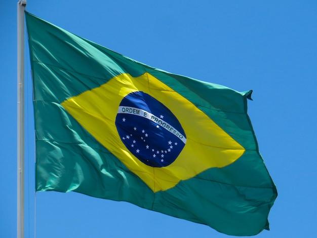 Bandiera del brasile che fluttua nel vento al centro della bandiera con le parole ordine e progresso Foto Premium