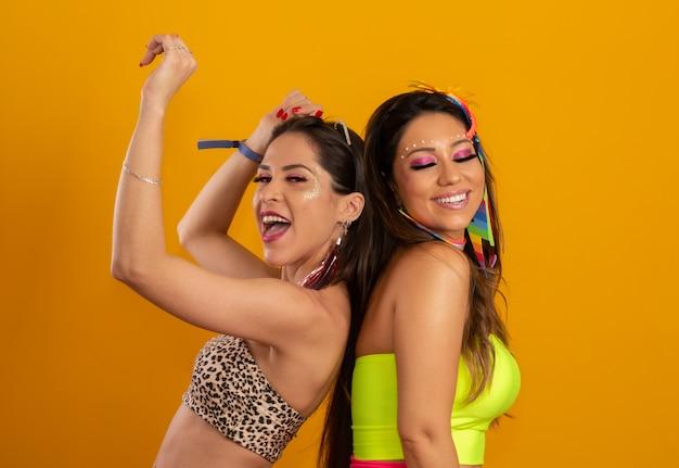 Carnevale brasiliano. due giovani donne in costume godendo la festa di carnevale. amici. Foto Premium