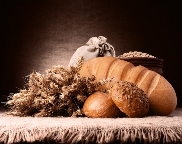 Pane, sacco di farina e orecchie a grappolo ancora in vita su rustico Foto Premium