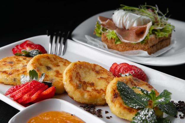 Colazione. torte di formaggio con pane tostato su un piatto bianco su una superficie nera Foto Premium
