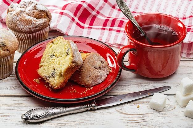 Prima colazione. muffin freschi e tè caldo in tazza rossa. Foto Premium