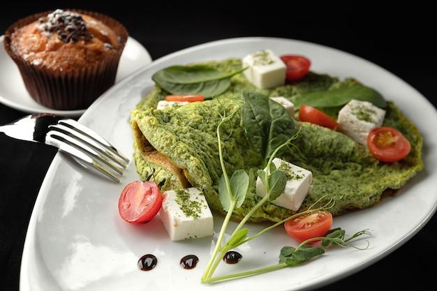 Colazione. frittata con spinaci e formaggio su un piatto bianco, su una superficie nera Foto Premium