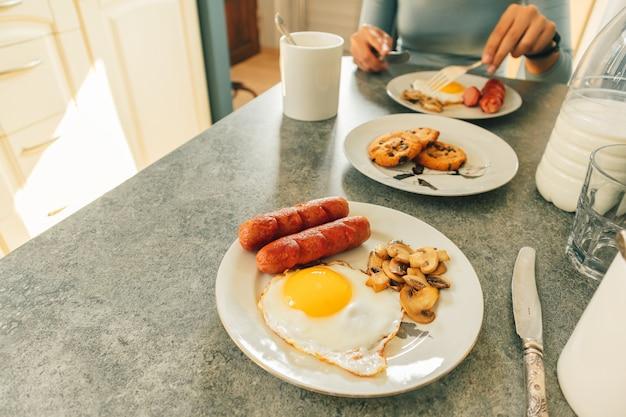 L'insieme della prima colazione delle uova fritte e del fungo delle salsiccie con latte fresco e biscotti è servito sulla tavola. Foto Premium