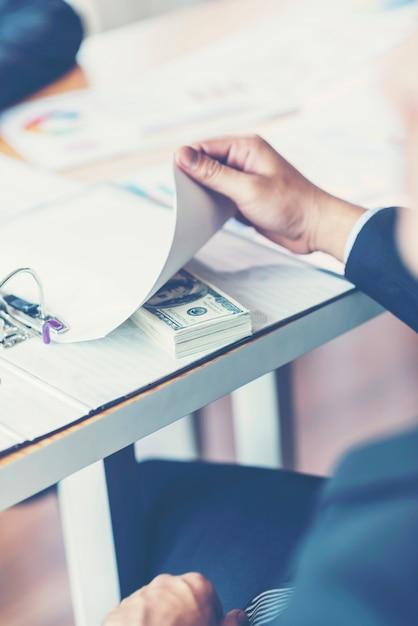 Concetto di corruzione e corruzione, tangente sotto forma di banconote da un dollaro Foto Premium
