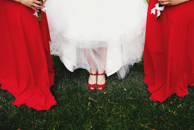 Sposa in abito bianco con damigelle in abiti rossi sull'erba verde. Foto Premium