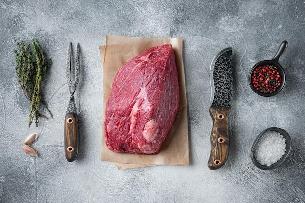 Petto di manzo carne cruda set con il vecchio coltello da macellaio mannaia, sul tavolo grigio, vista dall'alto laici piatta Foto Premium