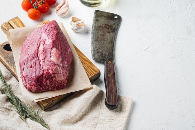 Petto di manzo carne cruda set, sul tagliere di legno con il vecchio coltello da macellaio mannaia Foto Premium