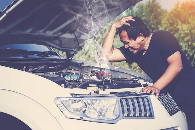 Una macchina rotta, motore aperto e fumo Foto Premium