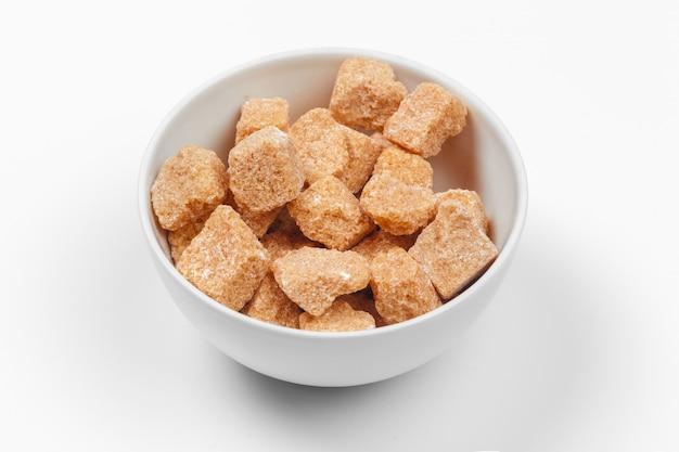 Cubi dello zucchero di canna di brown isolati Foto Premium