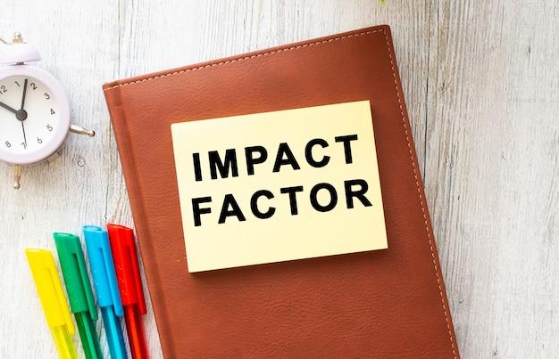 Blocco note marrone, adesivo con la scritta impact factor, penne colorate, orologio su fondo in legno. concetto di affari. Foto Premium