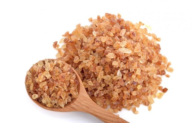 Zuccheri di roccia marroni in cucchiaio di legno isolato Foto Premium