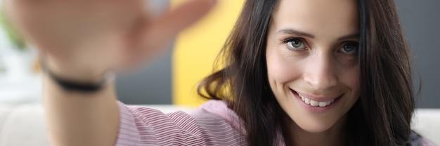 La donna castana sorride e saluta con la sua mano. Foto Premium