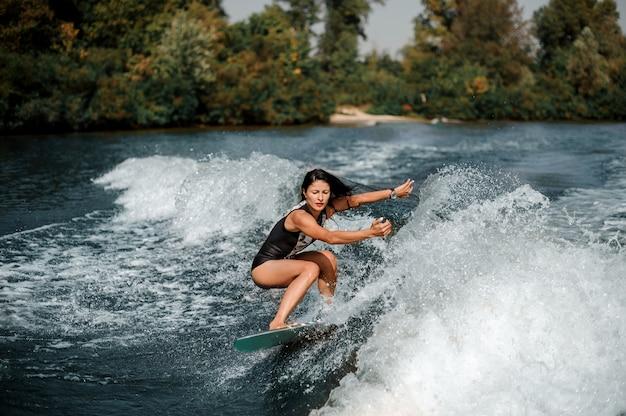 Donna castana che pratica il surfing a bordo giù l'acqua blu Foto Premium