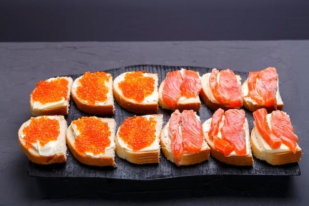 Bruschette con caviale di burro rosso e trota su una tavola di legno nera su sfondo grigio. foto orizzontale Foto Premium