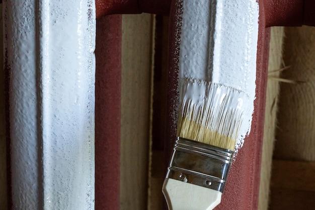 Pennello in vernice bianca macchia la batteria di ferro. Foto Premium