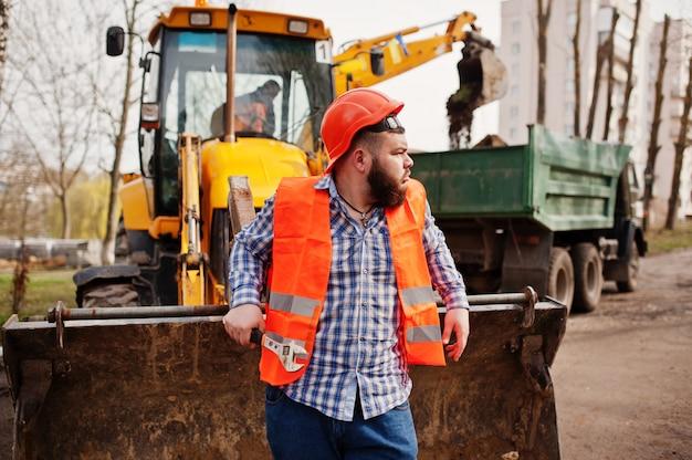 Brutal barba operaio uomo vestito operaio edile in casco di sicurezza arancione, contro traktor con chiave regolabile a portata di mano. Foto Premium