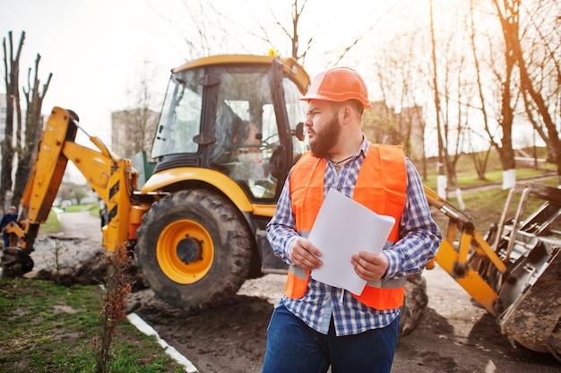 Muratore brutale del vestito dell'uomo del lavoratore della barba in casco arancio di sicurezza contro il traktor con la carta di piano a portata di mano. Foto Premium
