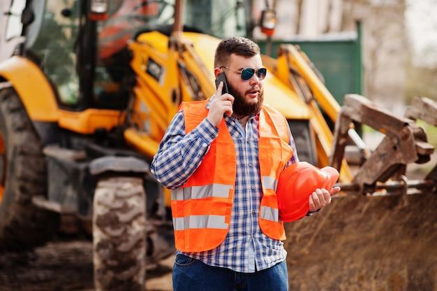 Brutal barba operaio uomo vestito operaio edile in casco di sicurezza arancione, occhiali da sole contro traktor con il telefono cellulare a portata di mano. Foto Premium