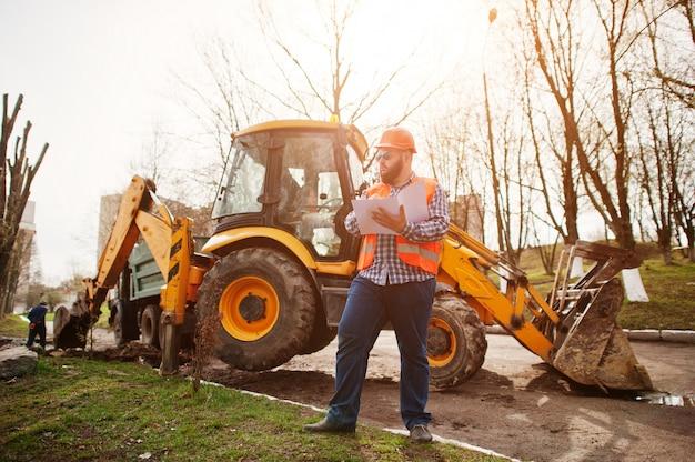 Brutal barba operaio uomo vestito operaio edile in casco di sicurezza arancione, occhiali da sole contro traktor con carta piano a portata di mano. Foto Premium