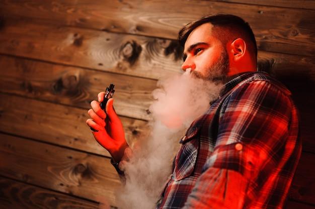 Uomo brutale che fuma sigaretta elettronica Foto Premium