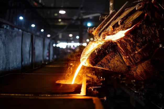 Benna con colata di ferro fuso caldo nello stampo, produzione e colata acciaio industriale, fusione, stampaggio e fonderia. Foto Premium