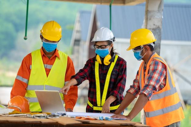 Costruttori che indossano il casco di sicurezza con il modello a costruzione, concetto di edificio residenziale in costruzione. Foto Premium