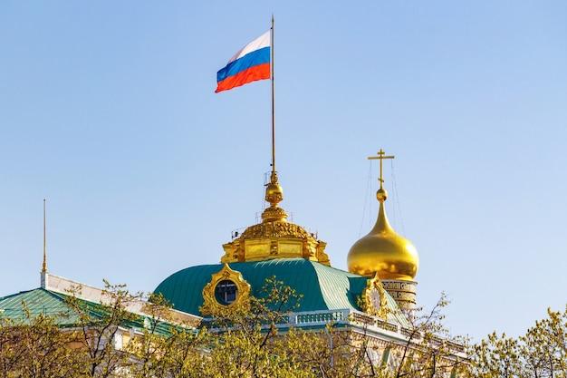 Costruzione del gran palazzo del cremlino con sventolando la bandiera della federazione russa sul tetto contro la cupola dorata della chiesa nella mattina di sole Foto Premium