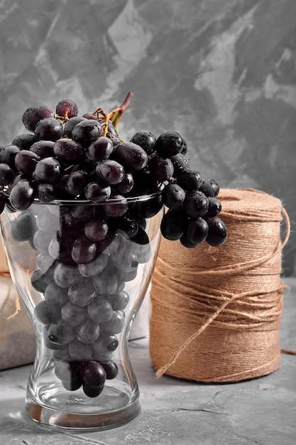 Grappoli di uve scure mature fresche su una superficie strutturale concreta uva da vino rosso natura morta di cibo natura raccolto autunnale Foto Premium