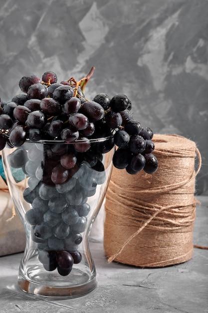 Grappoli d'uva rossa matura fresca su una superficie strutturale concreta Foto Premium
