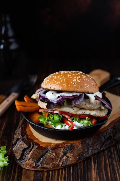 Hamburger con filetto di pollo alla griglia, paprika, patate dolci, lattuga, cipolle e yogurt greco Foto Premium