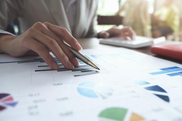 Concetto di contabilità aziendale, grafico indicante della penna dell'uomo di affari e facendo uso del calcolatore al bilancio calcolatore e carta di prestito in ufficio. Foto Premium