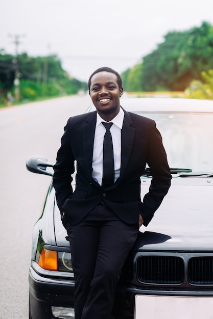 Uomo africano di affari in piedi davanti alla sua auto. Foto Premium