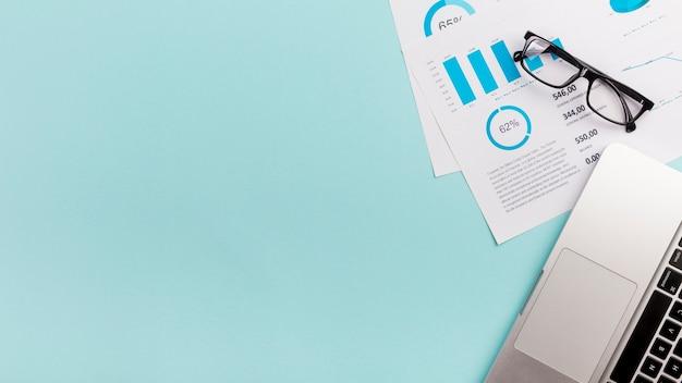Piano, occhiali e computer portatile del bilancio aziendale su fondo blu Foto Premium