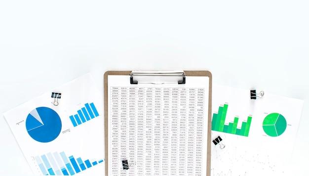Concetto di affari. documentazione finanziaria, diagramma verde e blu su fondo bianco. piatto di carta gialla. Foto Premium